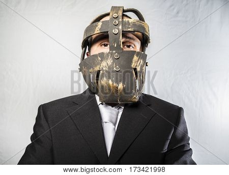 Dark Angry businessman with iron mask on his face, is dressed in suit and tie