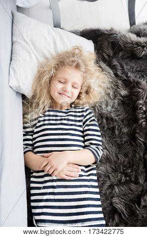Little girl with white curly hair in a striped vestin bed. Little girl having fun. Girl pretending to sleep. Little girl laughing