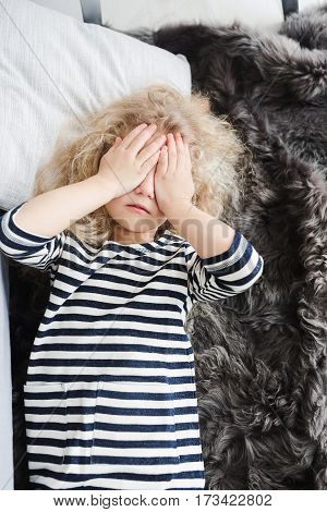 Little girl with white curly hair in a striped vestin bed. Little girl having fun. Girl pretending to sleep. Girl covered her face with hands