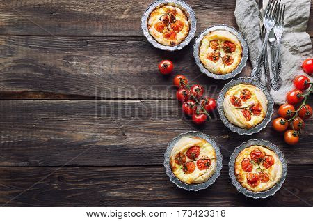 Fresh homemade tarts with cherry tomatoes and goat cheese on rustic wooden background. Top view.