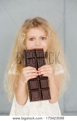 Little girl with white curly hair in a white lace dress is eating a large bar of chocolate on a blue background.