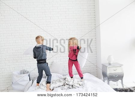 Little boy in gray pajamas and girl in curly hair in pink pajamas pillow fighting on the bed. Boy and girl having fun in the bedroom. Brother and sister. Boy and girl with blond hair