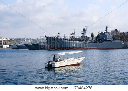 Sevastopol, Crimea - September 14, 2016. Several military ships at berth in Sevastopol Bay. A small motorboat.