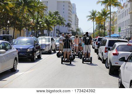 MIAMI BEACH, USA - FEBRUARY 26, 2017: Image of a group of tourists riding on segways along Ocean Drive South Beach Miami FL, USA