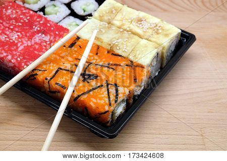 Sushi pieces on square tray on brown wooden table side view closeup