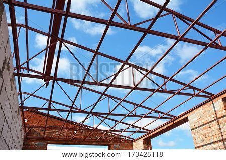 Steel roof trusses details with clouds sky background. Steel roof trusses sitting on concrete pole view from inside