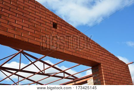 Steel roof trusses details with clouds sky background. Steel roof trusses sitting on concrete pole view from inside. Roofing construction.