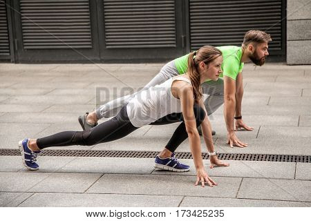 Young sport couple in starting position prepared to compete and run. using sport tracker.