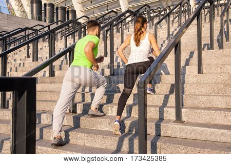 fitness sport people exercising and lifestyle concept - couple running upstairs on city stairs