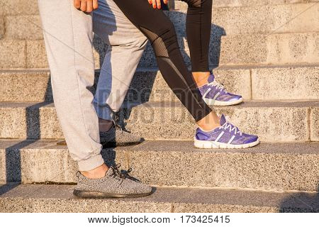 running couple resting. Closeup of running shoes and girl standing with boyfriend during jogging workout training outdoors on steps to relaxing.