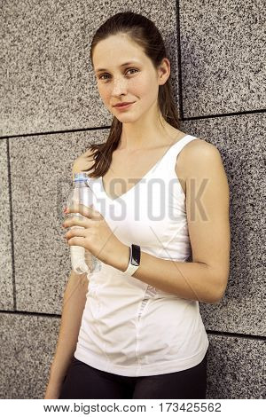 Fitness beautiful woman with freckles on her face drinking water and sweating after exercising in city. Female athlete after work out. looking at camera and smilling.