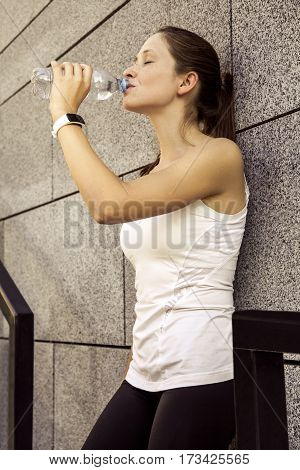 Fitness beautiful woman with freckles on her face drinking water and sweating after exercising in city. Female athlete after work out.