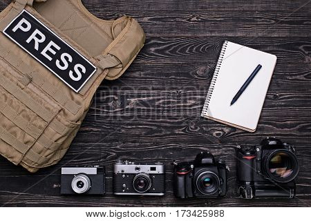 Bulletproof vest,retro and DSLR camera,notebook with pen on dark wooden table.Top view