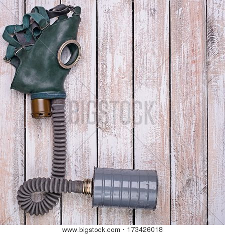 Gas mask with rubber tube and filter for air on light wooden background
