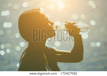 Silhouette of a young female athlete in tracksuit drinking water from a bottle on the beach in summer during morning exercises. Sport and healthy lifestyle.