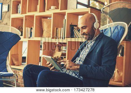 Businessman on coffee break listening to music via digital tablet and headphones