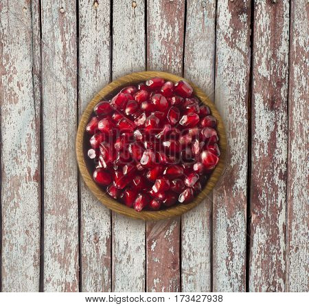 Pomegranate seeds in a wooden bowl. Top view. Red grains of a pomegranate on a wooden background. Pomegranate on wooden table with copy space