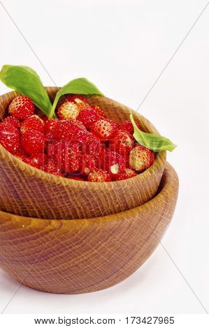 Wild strawberry in a wooden bowl. Ripe and tasty strawberry isolated on white background. Sweet and juicy berry. Berry useful for strengthening the immune system.