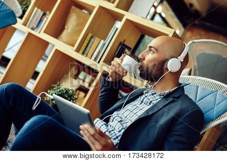 Modern man drinking coffee in a cafe hodling digital tablet and have headphones
