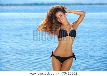 Young, Attractive, Smiling Slender Girl With Curly Hair In A Black Bathing Suit On The Beach.