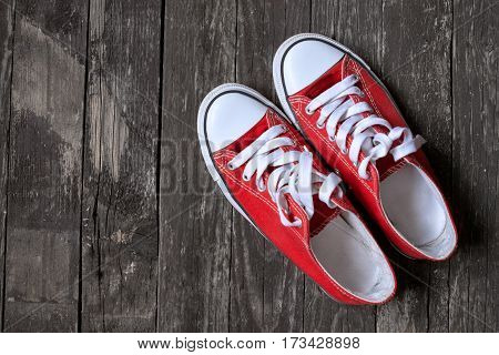 red sneakers on old wooden background. Concept of Sport Work out Training.