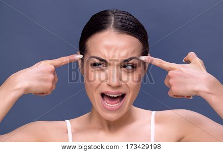 young woman checking wrinkles on her forehead- Beauty skin care