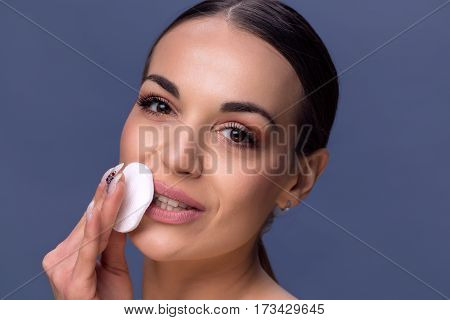 Beauty skin care. Beautiful happy woman removing face makeup using cotton pad. Close up portrait of healthy smiling female model with natural makeup touching perfect fresh soft skin cleaning her face