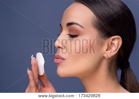 Beauty skin care. Beautiful happy woman removing face makeup using cotton pad. Close up portrait of healthy female model with natural makeup touching perfect fresh soft skin cleaning her