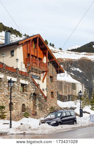 SOLDEU ANDORRA - FEBRUARY 7 2017: Street of Soldeu ski resort in the winter. Houses from a stone wet asphalt in the distance the mountains covered with snow