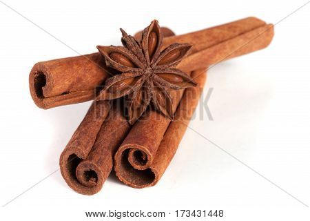 three cinnamon sticks with star anise isolated on white background.
