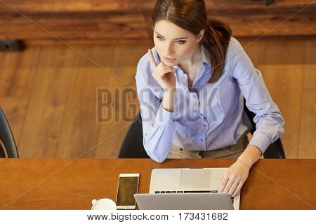 Top view of attractive business lady in formal clothes ,working and  relaxing while sitting at her working place in office