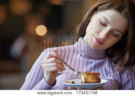 Beautiful woman eating chocolate cake at cafe