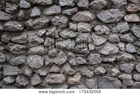 The wall made of gray stones and cement.