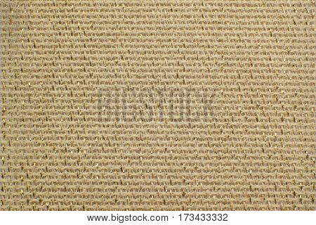 Beige natural linen fabric with brilliance golden lurex close-up. Aida texture for the background