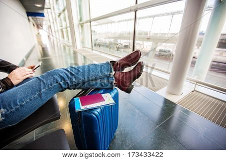 Passenger traveler woman using tablet smart phone in airport waiting for air travel .Young woman sitting with travel suitcase trolley in waiting hall of departure lounge in airport
