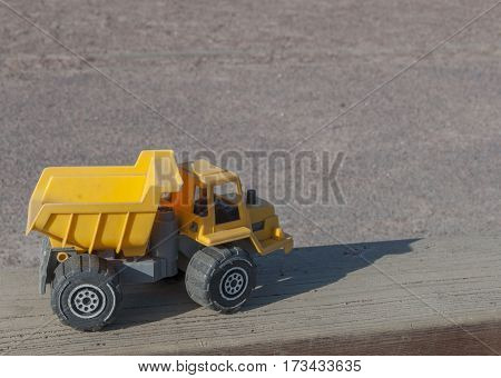Toy construction dumper background, building industry and childrens playground