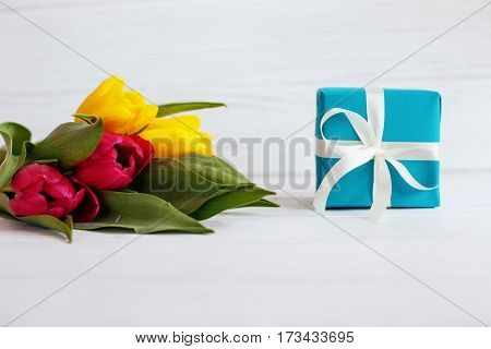 Flowers and a box with a gift. Concept of holiday birthday Easter March 8.