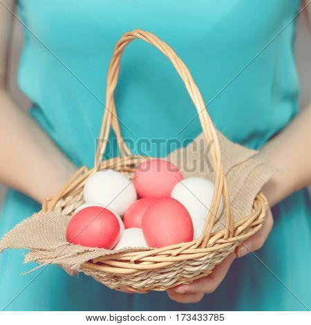 Easter Egg. Girl holding a basket with Easter eggs. Easter eggs lying in a basket. Easter ideas. Happy easter.Toned image.