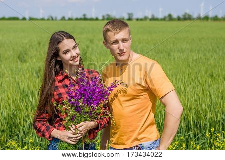 Beautiful Girl And Guy On Field With Wildflowers