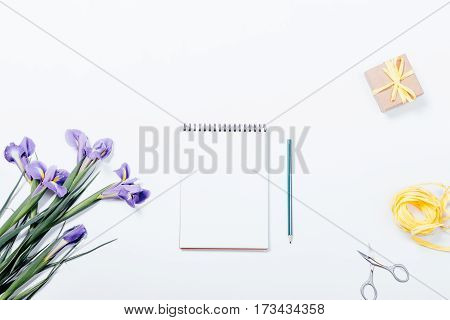 View From The Top Of A Bouquet Of Irises, A Notebook With A Pencil, Gift Box, Scissors And Ribbon