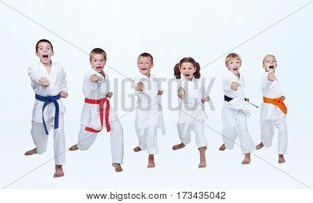 On a light background six karateka beating punch arm