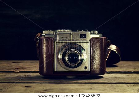 Old Vintage Camera on Dark Wooden Background. Horizontal with Copy Space.