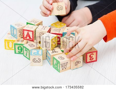 children playing with wooden cubes with letter and number