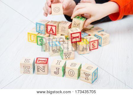 the enjoy written on wooden cubes on white