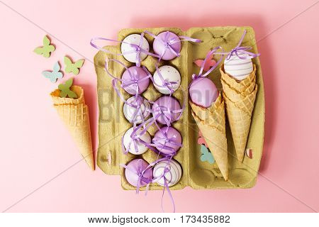 Easter or Spring Food Concept. Fresh Eggs in Box for Eggs with Ice Cream Cones on Pink Pastel Background. Top View.