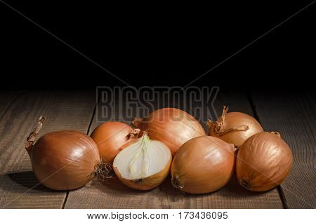 Raw onion is laying on an old wooden table and a black background. Plenty of space for text.