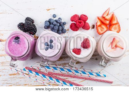 Selection of colorful detox berry drinks on wood background, copy space
