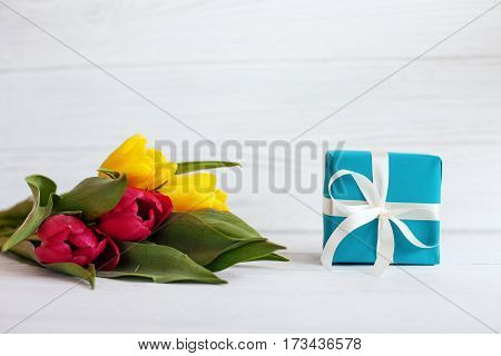 Flowers tulips and a box with a gift. Concept of holiday birthday Easter March 8.