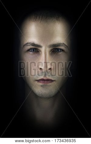 Contrasting male portrait on black background. Light and shadow on the man's face. Stylish brutal man art photo. Silhouette face serious macho expressive eyes