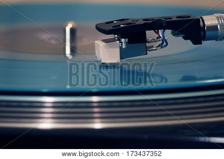 Closeup view of a stylus that traces the groove on a rotating vinyl record on a phonograph. The motion of stylus are converted into an analogous electrical signal by a transducer to produce sound.